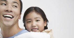 Closeup of a young girl getting piggyback ride with father